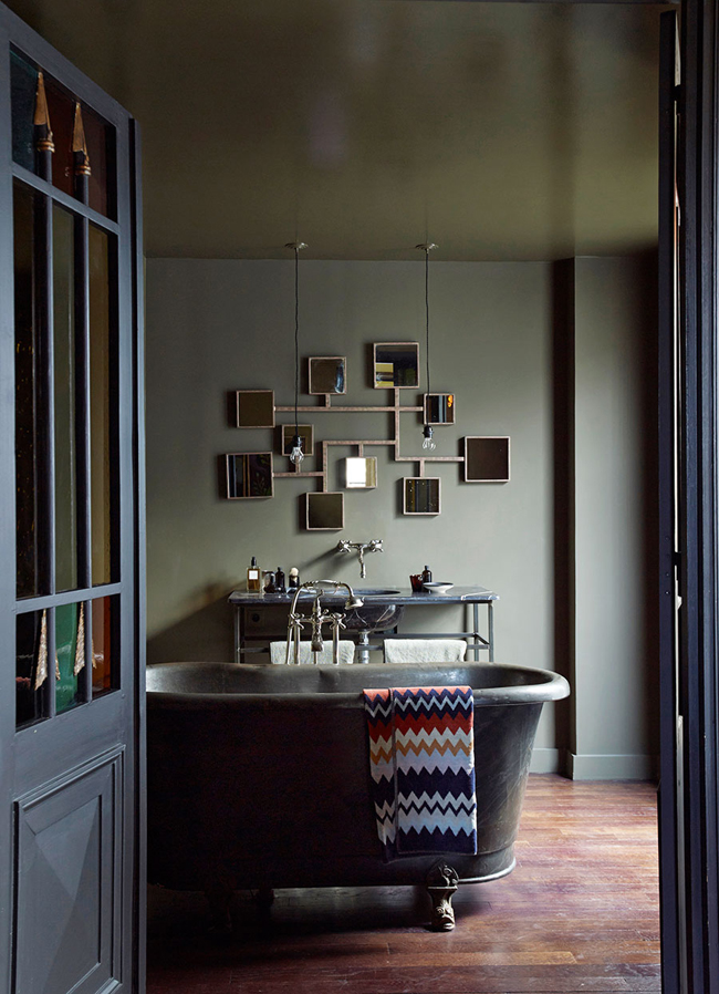 06-The-master-bathroom-strikes-with-a-mirror-installation-and-a-worn-vintage-bathtub-and-countertop