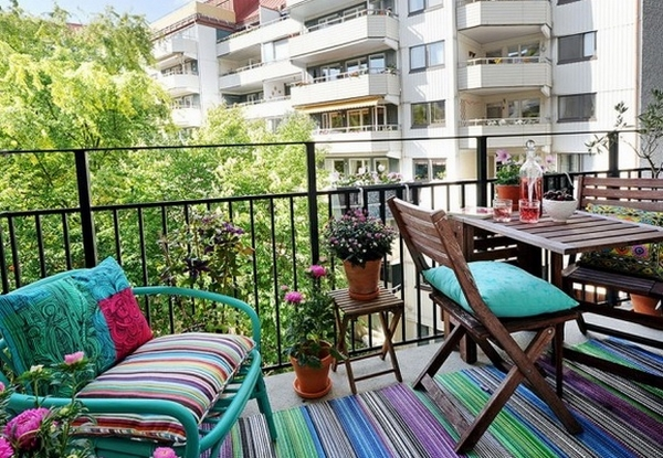 small-balcony-decoration-ideas-two-seater-sofa-wooden-table-colorful-carpet-upholstery