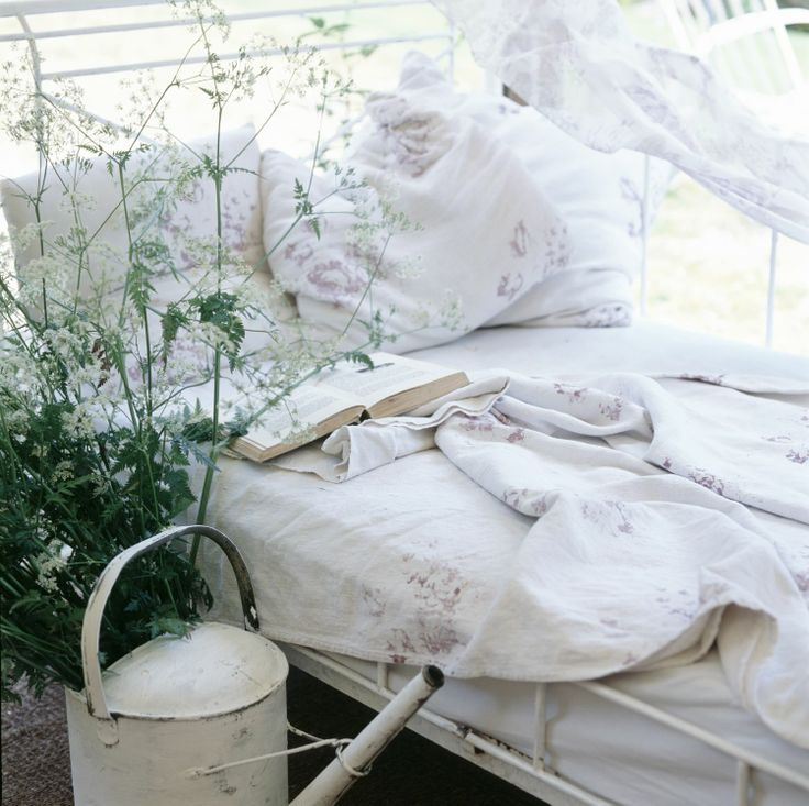 Vintage style daybed in garden summer house with floral linen