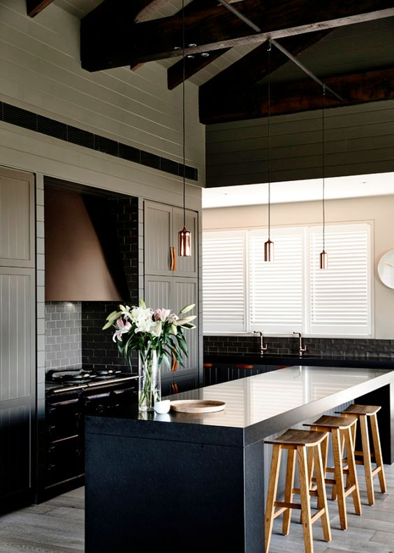 moody-kitchen-with-dark-panelled-cabinetry-and-leather-pulls