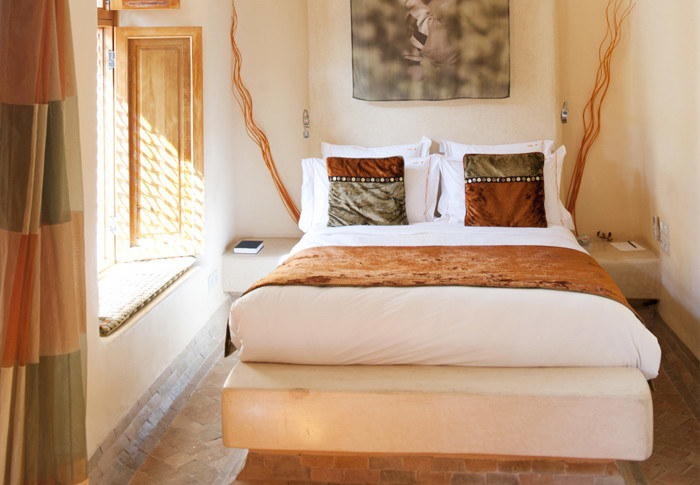 02-This-Africa-inspired-bedroom-has-light-walls-and-various-shades-of-ocher-used-for-decor-and-textiles