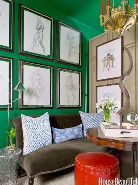 07-An-emerald-accent-wall-is-balanced-with-a-leather-ottoman-in-a-neutral-colored-room