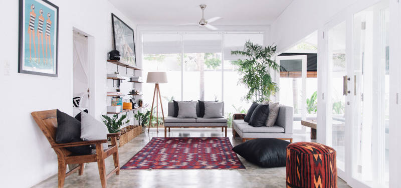 08-The-lounge-space-is-decorated-with-a-bold-rug-and-lots-of-island-potted-greenery
