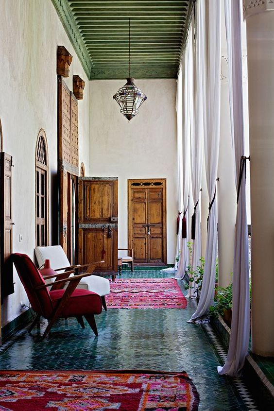 09-Moroccan-hallway-with-green-tiled-floor-and-red-rugs-and-chairs