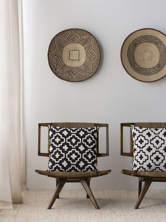 11-Dark-wood-chairs-upholstered-with-ethnic-woven-fabrics-and-matching-pottery-on-the-wall
