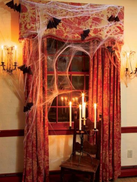 21-Halloween-window-decor-with-faux-spiderweb-bats-and-a-vintage-candle-holder