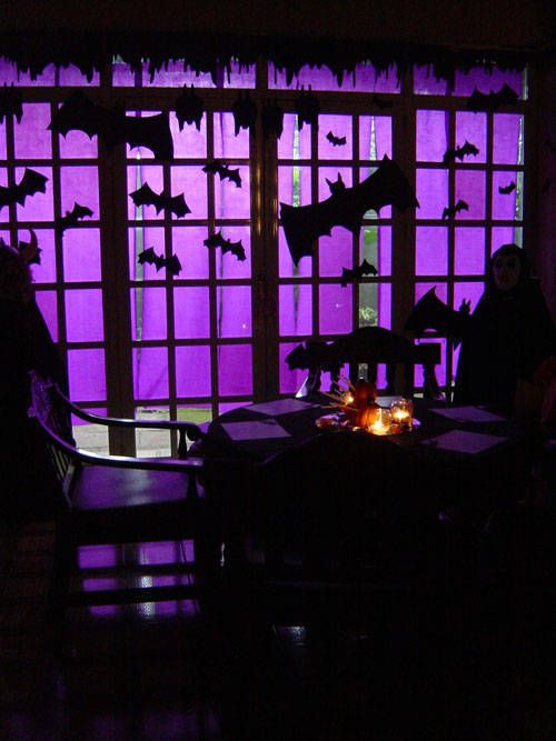 26-use-purple-crepe-paper-to-cover-a-large-window-or-glass-door-and-then-cut-up-black-bats-in-different-sizes