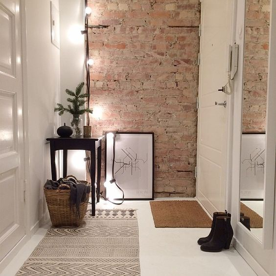 02-small-decluttered-entryway-with-an-exposed-brick-wall-lights-and-a-tall-mirror