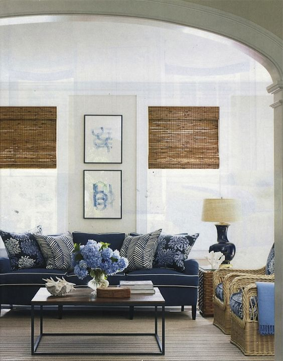 06-elegant-beachy-cottage-living-room-design-with-soft-sand-walls-paint-color-bamboo-roman-shades-blue-cushion-sofa-with-white-piping-brickmakers-coffee-table-wicker-chairs-with-blue-cushions