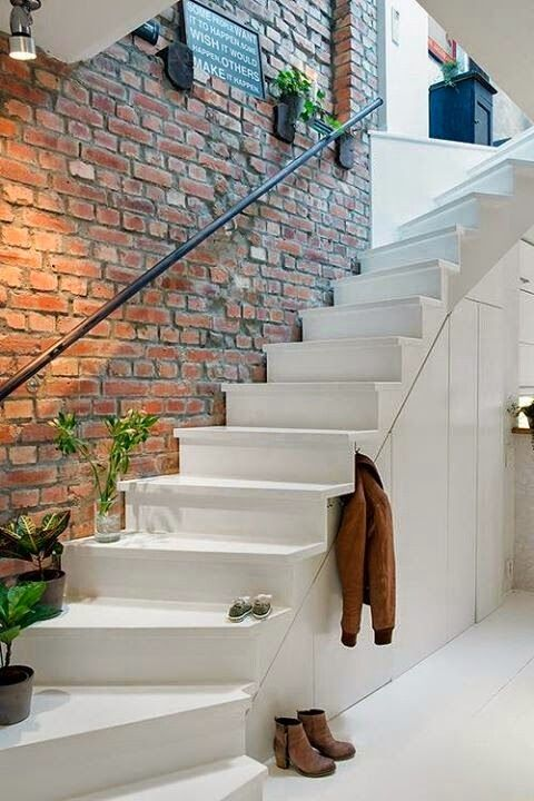 11-exposed-brick-wall-above-the-stairs-gives-a-style-to-this-entryway