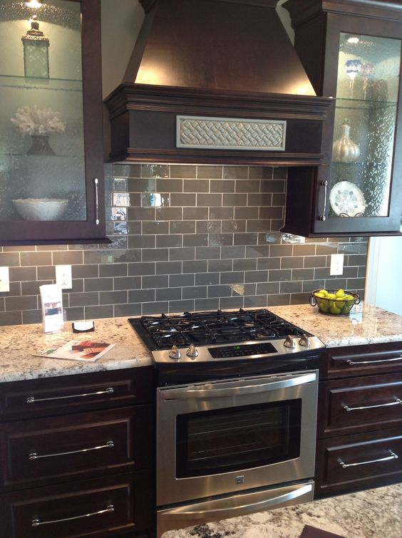 24-gray-glass-subway-tile-backsplash-with-dark-brown-cabinets-and-stainless-steel-appliances
