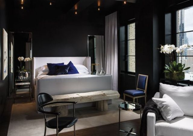 dark-bedroom-with-a-crispy-white-bed-and-a-raw-bench-for-a-contrast