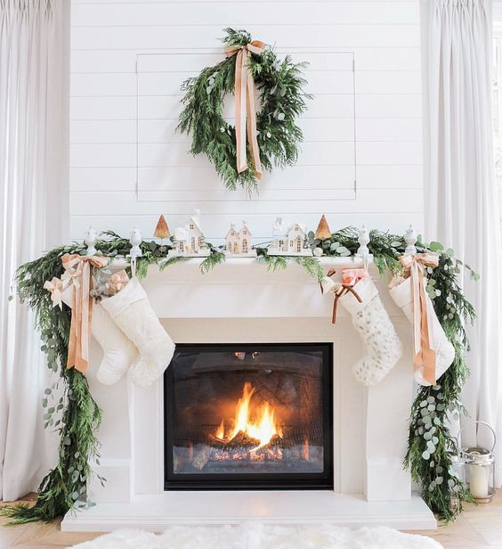 03-evergreen-garland-and-wreath-bows-and-small-houses-make-the-fireplace-very-cozy