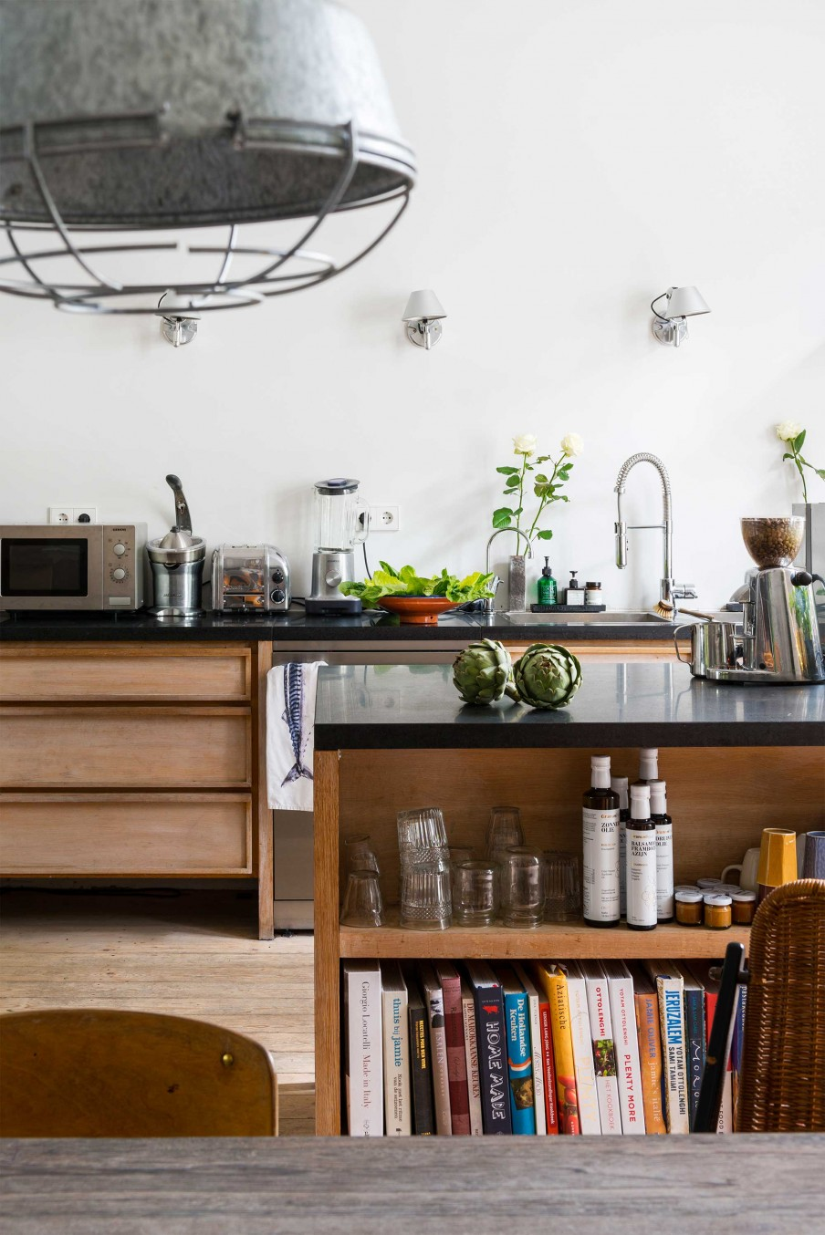 05-The-kitchen-features-sleek-black-surfaces-wooden-cabinets-and-floor-its-filled-with-light-and-not-as-whimsy-as-other-areas