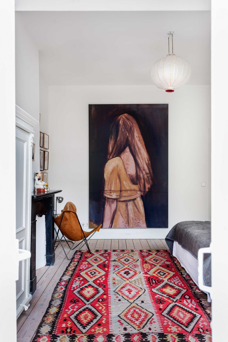 06-The-bedroom-boasts-of-colorful-boho-textiles-artworks-a-black-fireplace-and-a-mid-century-leather-chair