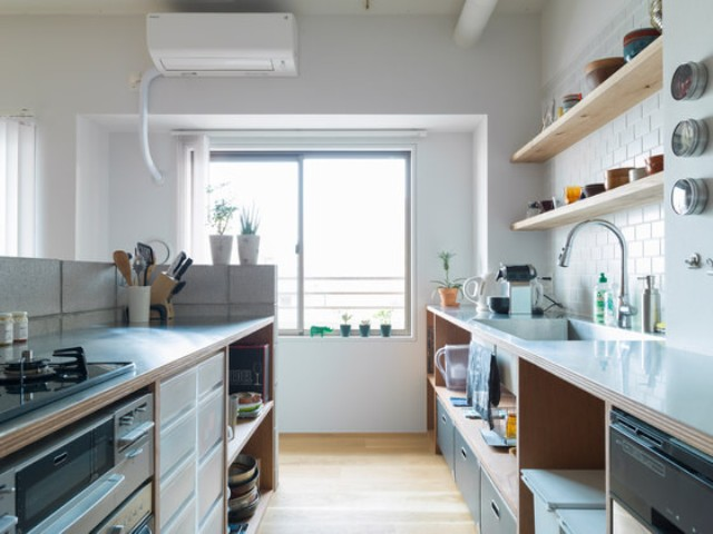 05-The-kitchen-is-minimalist-with-white-and-warm-wood-sleek-surfaces