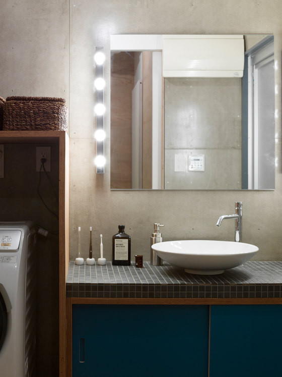09-The-bathroom-is-done-in-concrete-small-tiles-and-blue-shades