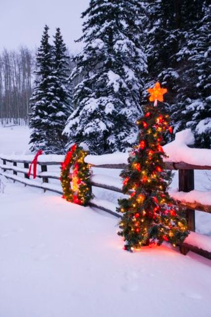 33-fence-decorated-with-a-lit-up-wreath-and-a-Christmas-tree-on-it