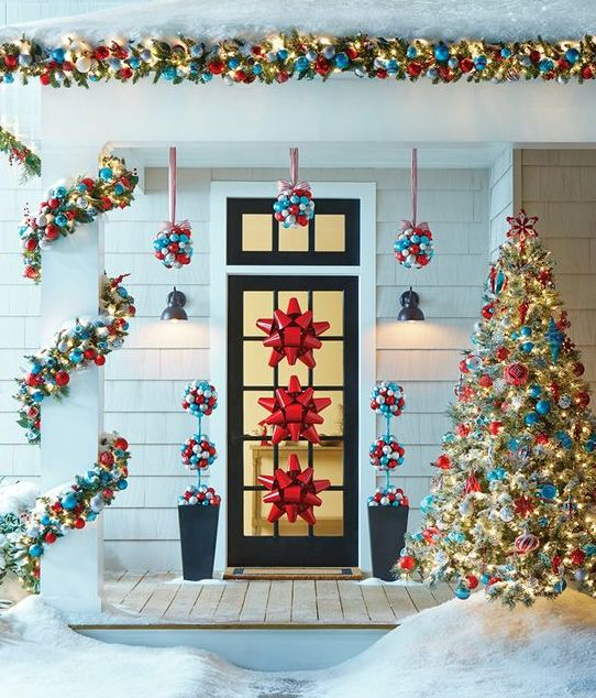 39-ornament-topiaries-hanging-over-the-door-garlands-and-red-bows-on-the-door